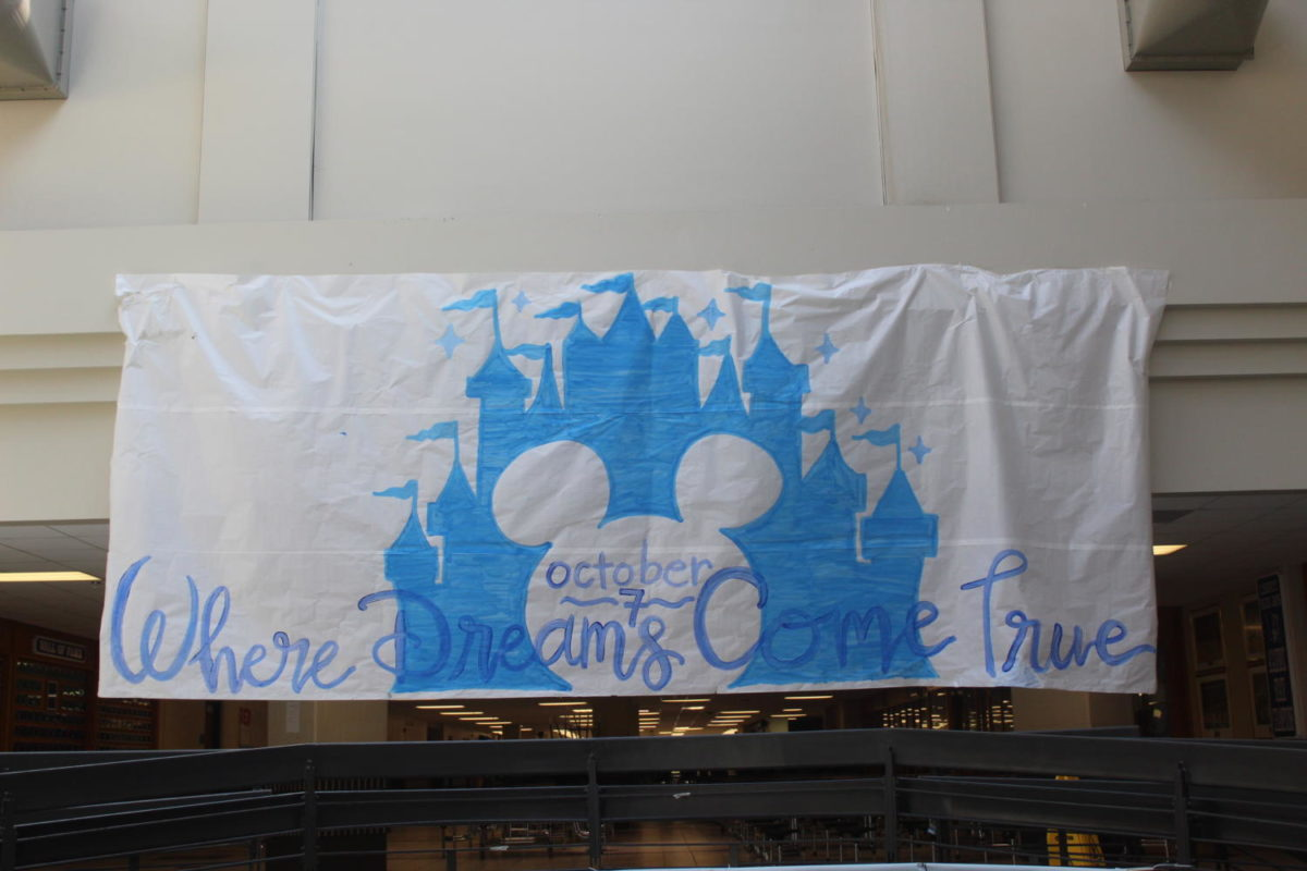 StuCo+members+advertise+the+Disney+themed+homecoming+with+a+banner+in+the+atrium%2C+promoting+the+dance+on+October+7.+Photo+by+McKenna+Hegger