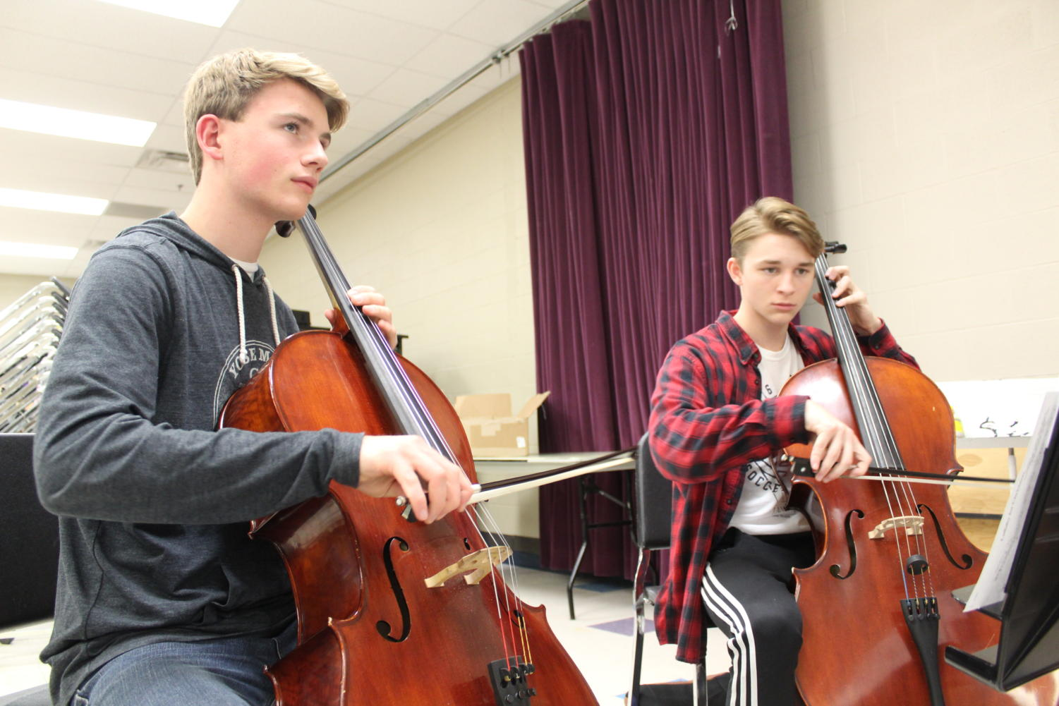 Junior William Laycock and senior Jack Fulkerson play their cellos during a symphonic orchestra rehearsal. Photo by Chrystian Noble