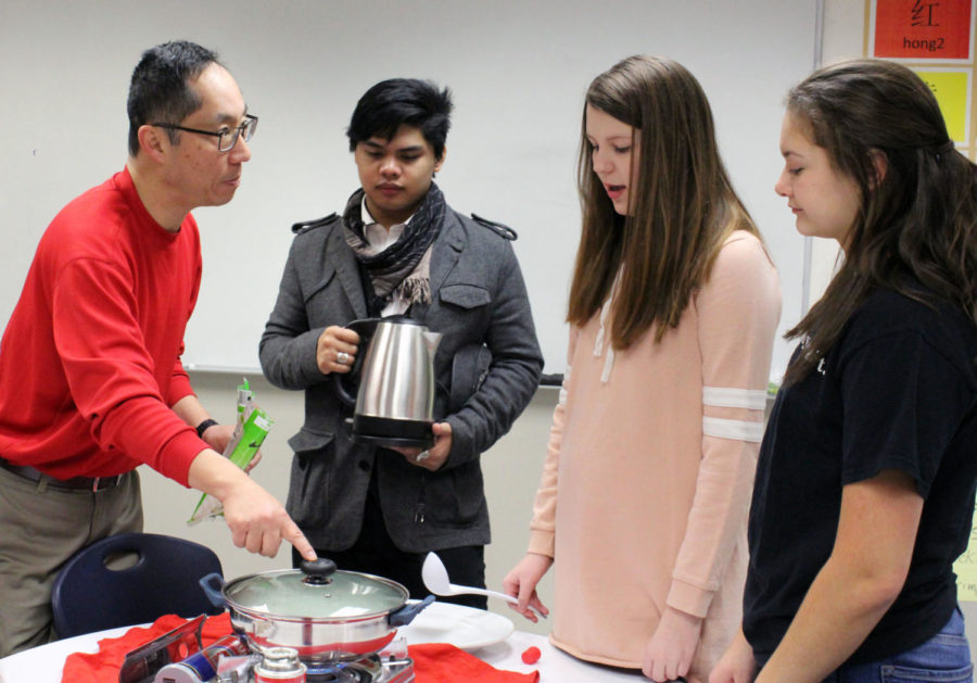 Chinese teacher Shianguu Hsieh encourages senior Liam Arciga and freshmen Kora Wiedmaier and Audrey Fulkerson to try new Chinese foods in his classroom on February 5. Photo by Mercedes Peck
