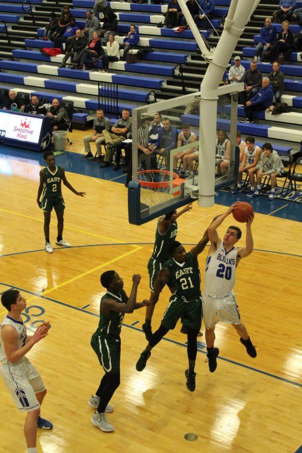Junior Kellen Goodwin scores against a player from Kansas City East High School. Photo by Kylee Williams.